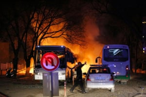 A police officer gestures and firefighters try to extinguish flames after a car bomb detonated in Ankara, Turkey