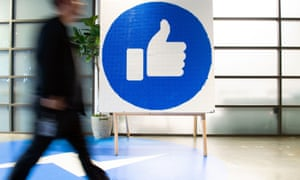 A Facebook employee walks by a like sign