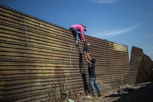 Central American migrants climb the border fence between Mexico and the US.