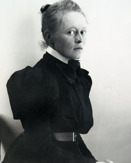 Black and white image of blonde woman, her hair tied back, looking perhaps apprehensively at viewer