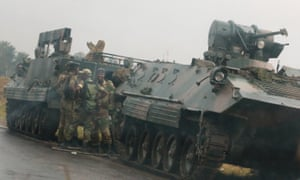 Soldiers standing besides armoured vehicles outside Harare, Zimbabwe