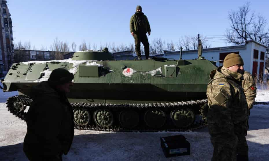 Ukrainian medical troops by an armoured personnel carrier after taking wounded servicemen to hospital in Donetsk.