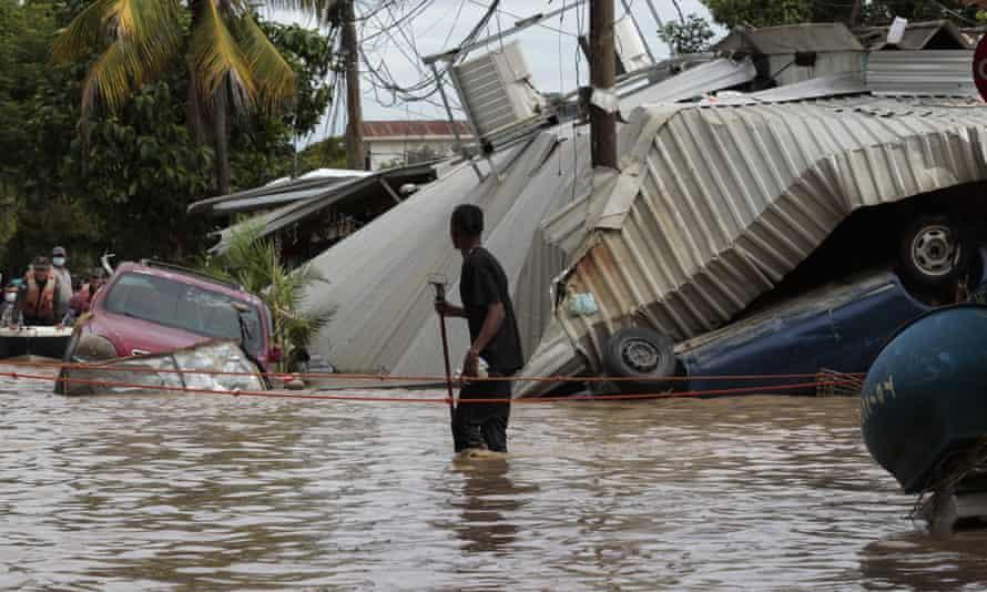 A man walks through a flooded street caused by Hurricane Eta in Planeta, Honduras, in 2020