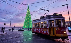 A tram drives past the fully lit Christmas tree in the almost deserted Praça do Comercio,