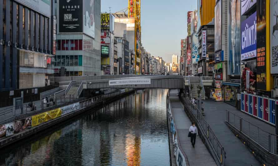 A man wearing a face mask walks alongside the canal in osaka, japan
