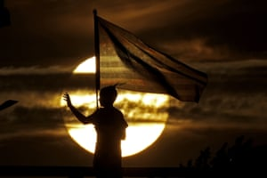 A boy holding a US flag waves to passing traffic in front of a setting sun