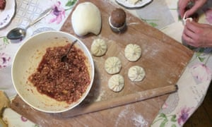 Learning to make khinkali dumplings at Ketino Sujashvili's guesthouse – a board with a ball of dough, a bowl of filling and small parcels