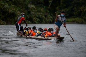 Punters push boat full of people across river