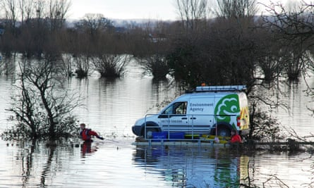 Environment Agency employees float their van on a pontoon raft along a flooded road on the Somerset Levels, UK