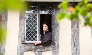 An actor in period dress at an upper floor window at Shakespeare's Schoolroom, Stratford-upon-Avon, UK