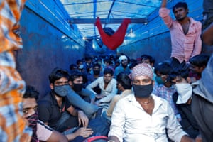 Migrant workers in Ahmedabad board a truck to return to their villages during a 21-day nationwide lockdown.