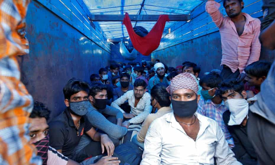 Migrant workers in Ahmedabad board a truck to return to their villages .