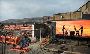 """""""Two men bow their heads in honour of slain loyalist paramilitaries"""" ... murals line the peace walls in the Shankill Road area of West Belfast."""