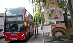 A London bus arrives at a bus stop displaying children's pictures made during the UK lockdown.