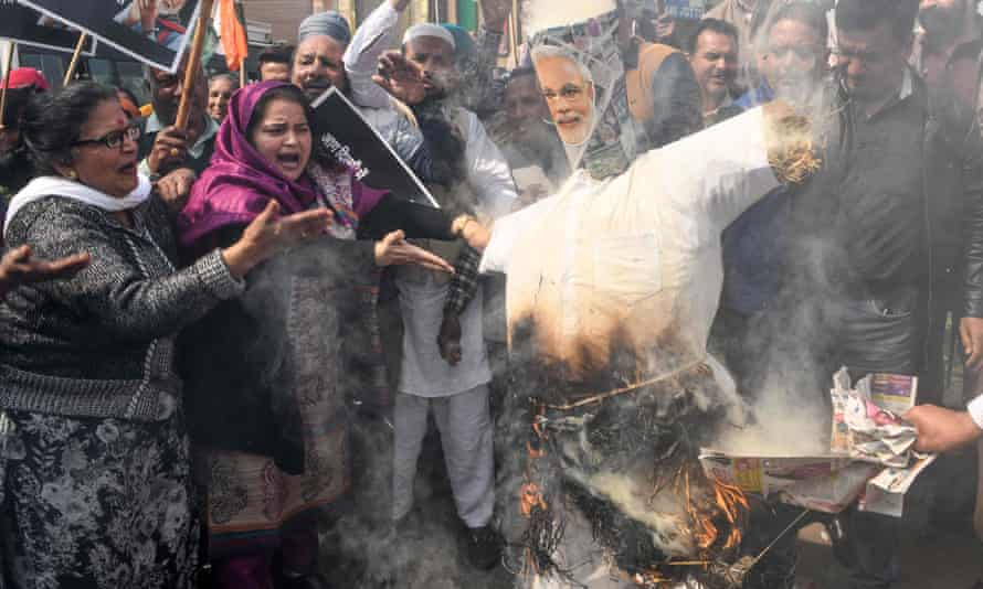 Congress party supporters in Amritsar burn an effigy of Narendra Modi during a demonstration to protest against the violence occurring in Delhi