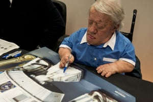 Kenny Baker signs film poster at a Comic Expo in Paris, France in 2014
