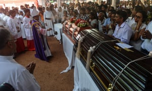 SRI LANKA-ATTACKSA Sri Lankan priest blesses the coffins of bomb blast victims during a funeral service at St Sebastian's Church in Negombo.