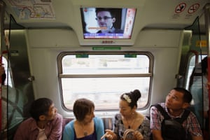 Train passengers in Hong Kong are shown TV images of Edward Snowden before his flight to Moscow in June 2013.