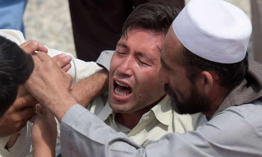 A victim's relative is comforted after Saturday's attacks in Kabul