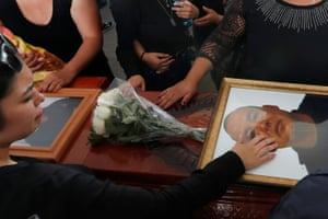 Relatives touch the coffin and photo of police officer Pablo Sergio Reynel, one of a group of officers killed in the line of duty, during a memorial service at the public security department headquarters for Michoacan, in Morelia, Mexico, Tuesday, Oct. 15, 2019. More than 30 suspected cartel gunmen ambushed the police officers in the town of El Aguaje on Monday as they were traveling in a convoy to serve a warrant, killing 13 officers and wounding nine others.