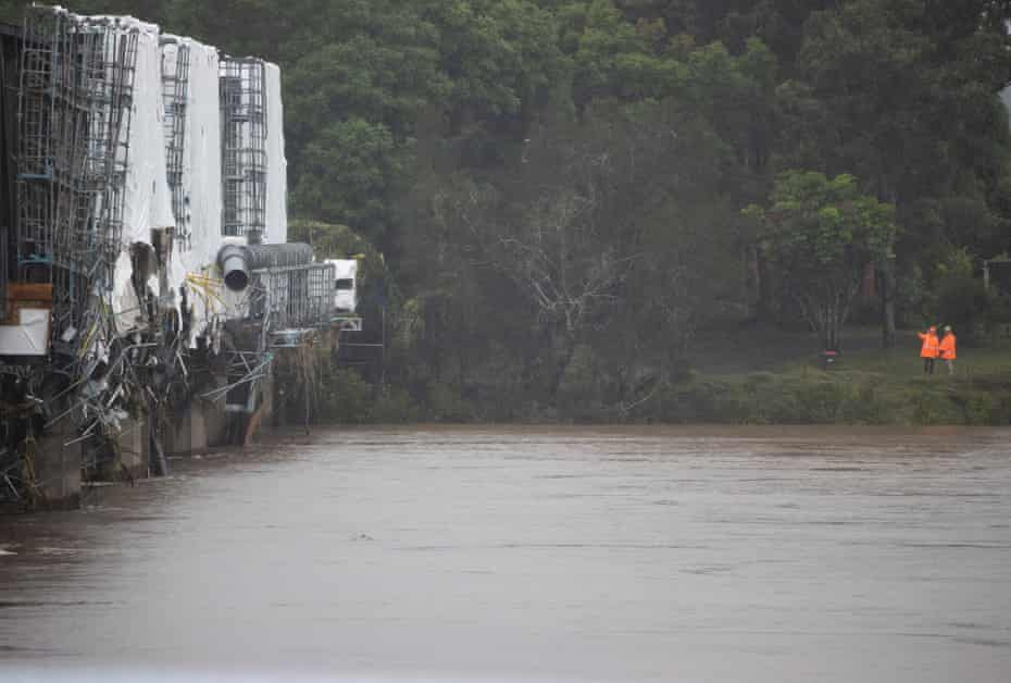 Workmen inspect a damaged bridge across the Manning River at Taree