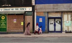 Women and a child walk along a Stoke street