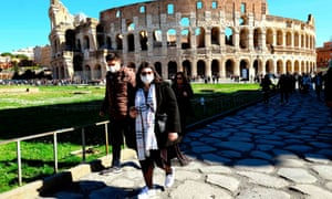 Tourists wearing masks to protect themselves against coronavirus at the Colosseum in Rome