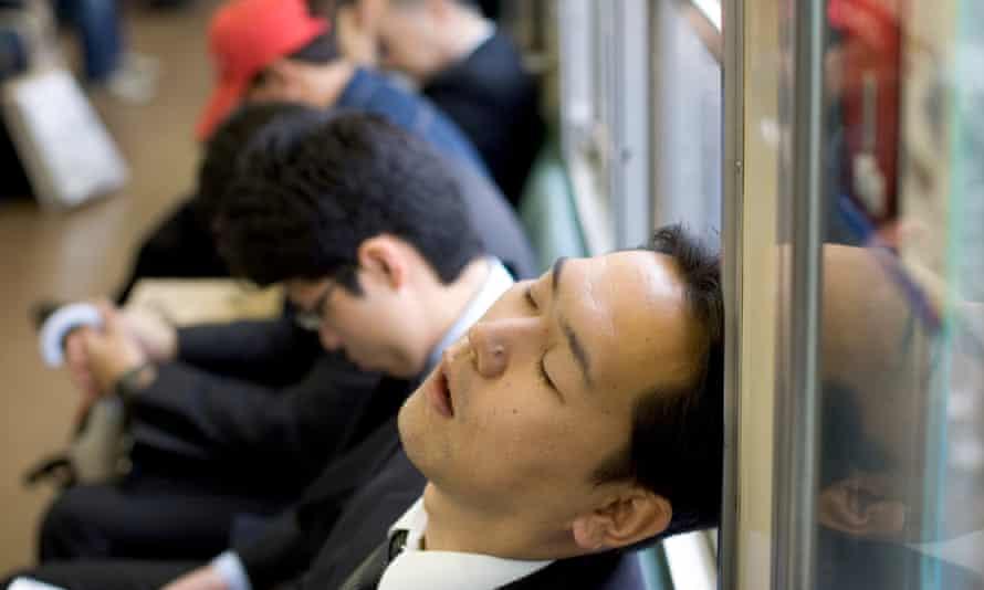 A commuter sleeps on the Tokyo metro.