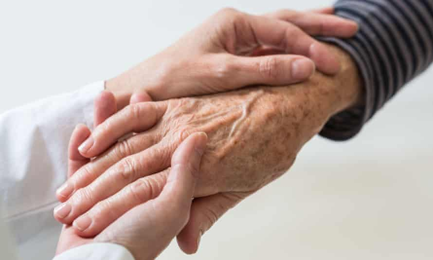 Younger woman's hands holding the hand of an older person.