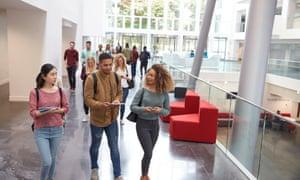 Students walk and talk inside a modern university building