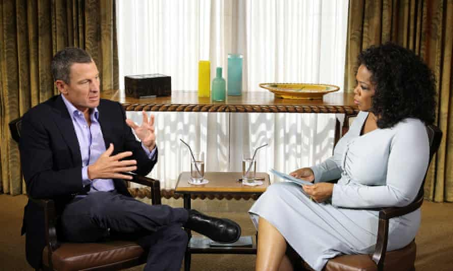 Armstrong in a dark suit and Winfrey in a light dress sit at a 45-degree angle to each other. They sit in a room with a sideboard at the back and two glasses of water on it.