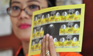 A post office employee displays a set of special stamps produced to commemorate the total solar eclipse in Jakarta.