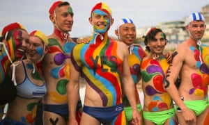 People with their bodies painted participate in an event at Tamarama beach supporting a yes vote in the same-sex marriage survey.