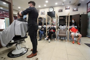 Hairdressers wash and cut the hair of customers in a hair salon, amid the coronavirus outbreak, in Louvain-La -Neuve, Belgium, on 5 March, 2021.