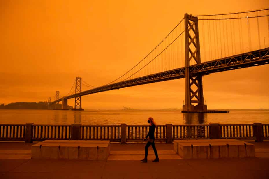 A woman walks under an orange smoke-filled sky in San Francisco on 9 September when more than 300,000 acres were burning across the north-western state including 35 major wildfires.