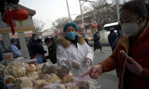 A woman wearing a face mask buys food from a stall set up by a restaurant outside its outlet in Beiing, China.
