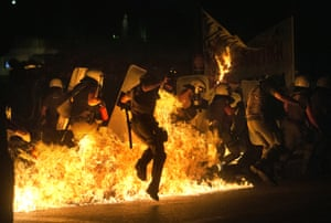 Riot police officers run through fire as protesters throw petrol bombs in Athens