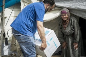 A woman in Alzouf camp, Syria, receives a food