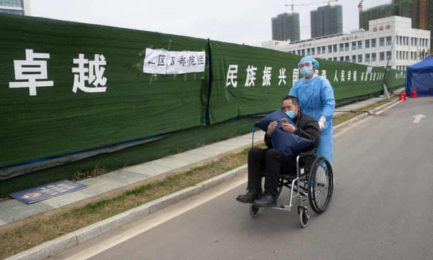 A medical worker pushes a coronavirus patient in a wheelchair in Wuhan
