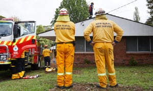 NSW Rural Fire Service workers repair the damage to a Sydney house after the city was hit by a hailstorm.