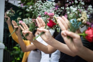 Demonstrators hold flowers in memory of the victims of the violent crackdown on protests against themilitary takeover during a 'flower strike'
