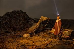 Woman stands in bleak landscape