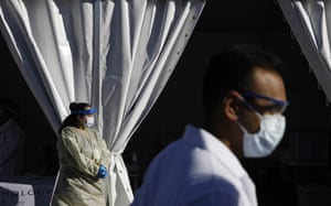 Healthcare workers with the University of Nevada Las Vegas School of Medicine wait in personal protective equipment for patients at a drive-thru coronavirus testing site in Las Vegas.