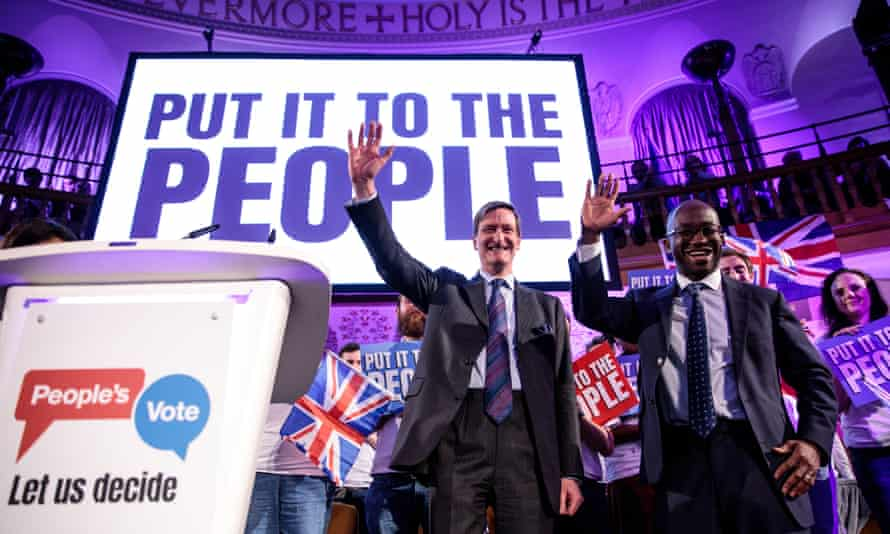 The two politicians wave in front of a crowd in a church and sign saying 'put it to the people'