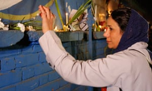 An Iranian woman in headscarf at a memorial oustide French embassy in Tehran to the victims of the Paris attacks