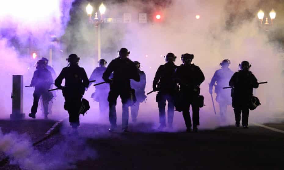 Police officers walk enveloped by teargas in Portland in March.