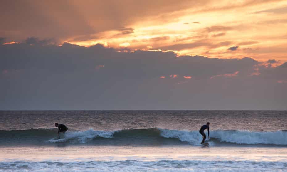 Evening surfers enjoy Llangennith beach in Rhossili Bay.