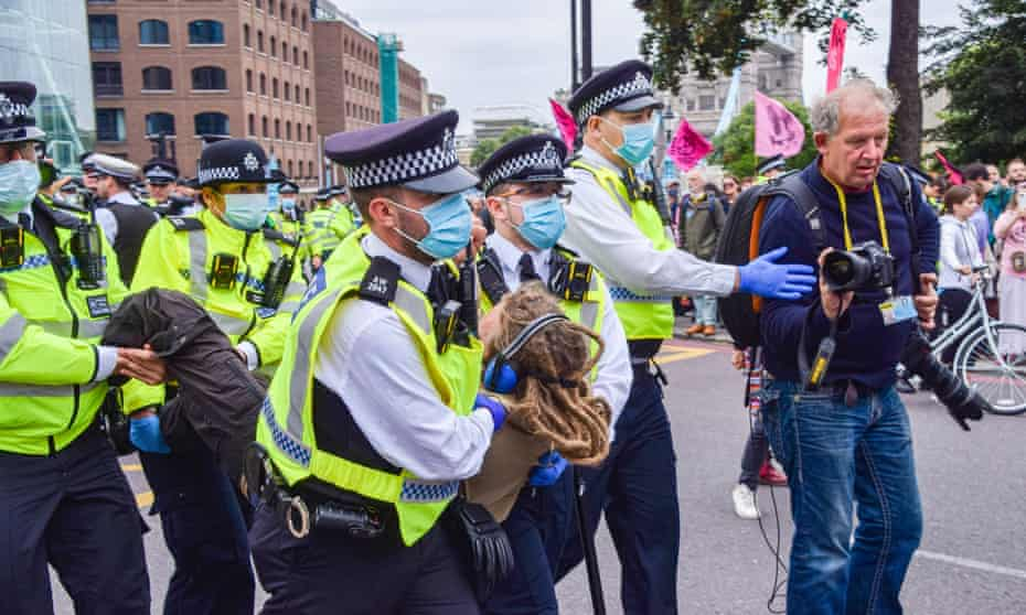 Police officers arrest a protester during an Extinction Rebellion demonstration in Tower Hill, London