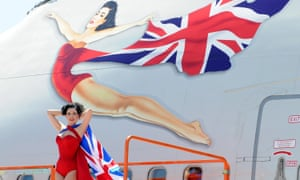 A model poses in front of the icon of a flying woman on a Virgin Atlantic plane on the tenth anniversary of the company.