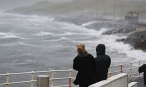 People watch the waves and sea spray in Lahinch, County Clare